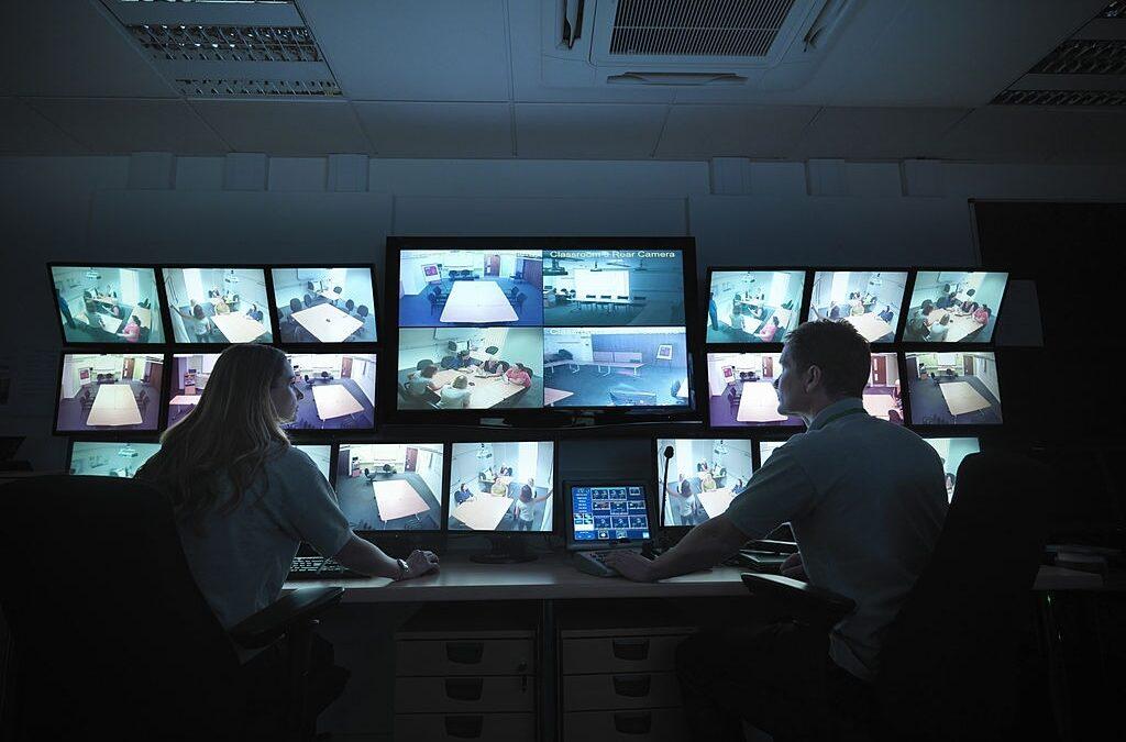 Pria dan wanita memonitor aktivitas di balik layar kaca